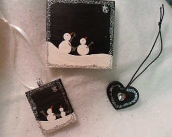 Snowmen and Heart ornaments. Set of three handmade and painted wood .2 snowmen ornaments, 1 heart. Silver glitter.