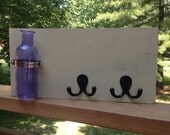Mounted purple vase sign with two black hooks