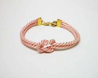 Light pink forever knot nautical rope bracelet with gold anchor charm