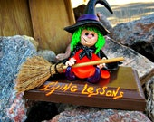 Adorable little witch patiently waiting for her very first flying lesson.