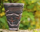 Viking mead or coffee cup with carved pattern representing Yggdrasil the big central ash tree in old Norse Cosmology