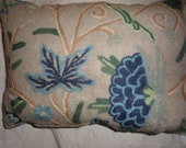 Blue and Green Crewel Work Lumbar Pillow on Burlap background