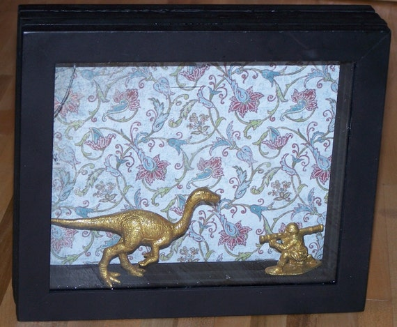 dollar store shadowbox with gold glittered dinosaur and soldier inside