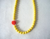 Yellow necklace with a red rose