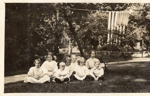 Vintage Real Photo Post Card of School Children Sitting Outdoors with USA Flag - Early 1900's