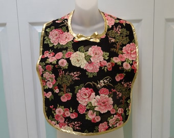 MAKE-UP BIB :  or cover-up ,black, with oriental pink flowers,lace vinyl backing and gold bias tape