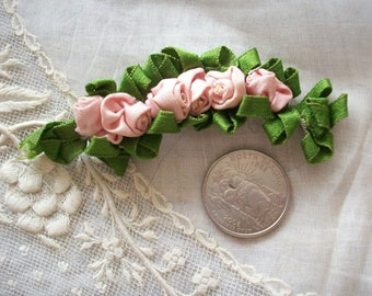 Ribbonwork pin of a series of dusty pink roses in one piece