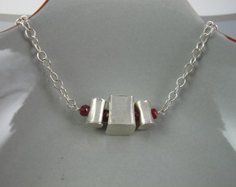Necklace with Ruby Rondelles. Hill Tribe Silver Prism and Cylinders are Strung Between Red Rubies, Sterling Silver Chain and Clasp