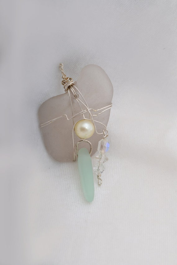 Sea Glass Jewelry  here.   Wire wrapped large piece of sea glass w pearl & crystals as a pendant.       FREE SHIPPPING