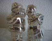 Silver or Chrome Color Salt and Pepper Santa and Mrs. Claus Kissing and Holding Presents Behind Their Backs