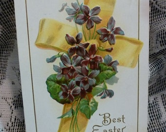 Vintage Best Easter Wishes.  Violets around a yellow ribbon cross. cprt 1909 H Wessler