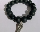 Black beaded bracelet accented with faceted beads and a sterling silver angel wing.