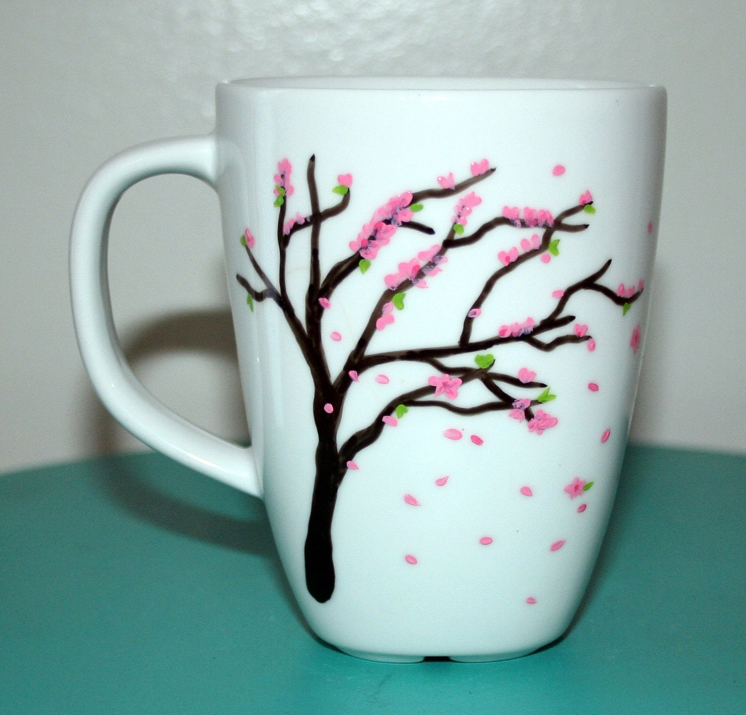 White ceramic mug hand painted with a wind blown pink cherry for How to paint ceramic mugs at home
