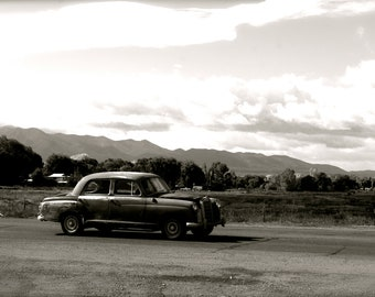 A black and white photo of a classic car, a landscape portrait of the desert, Taos New Mexico