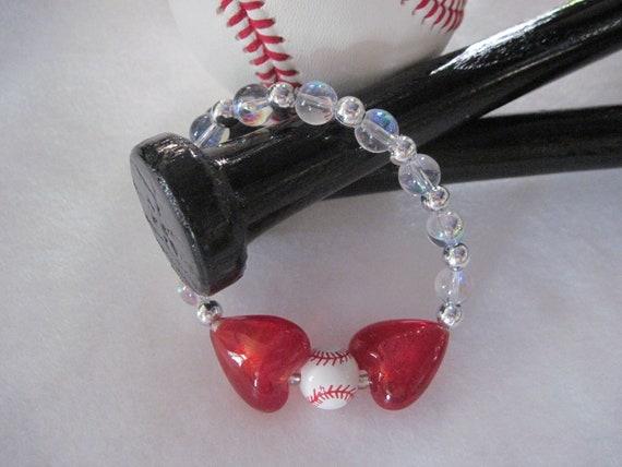 Baseball Bracelt. Black seam baceramic baseball huged by two crystal hearts. 2012019