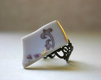 Broken china ring with gray swirls.