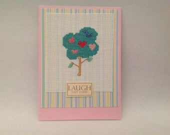 Tree and hearts cross stitch card handmade with an original design and the wording 'Laugh out loud'
