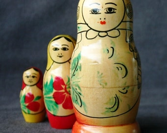 Three little vintage matryoshkas wooden dolls.