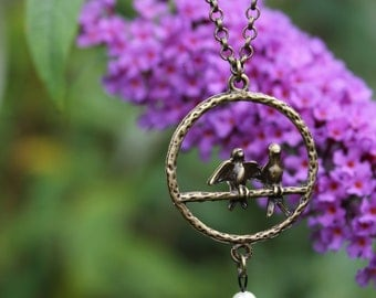 Necklace with birds sitting on a circular perch with pearl bead in vintage bronze 20""