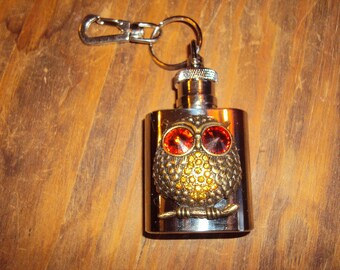 Chubby owl on a miniature flask