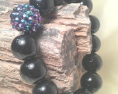 Black AB resin DISCO rhinestone ball is surrounded by black onyx gemstone as a stretchy bracelet