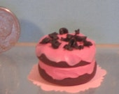 Miniature chocolate layer cake with pink frosting
