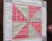 Red and grey table mat with Moda fabrics, pinwheel design, quilted, square.