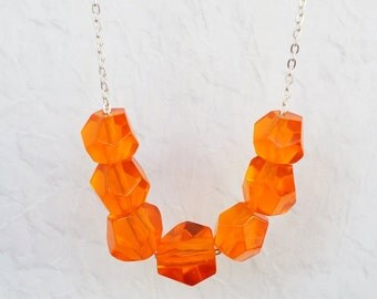 Clear Tangerine Orange geometric bead necklace.