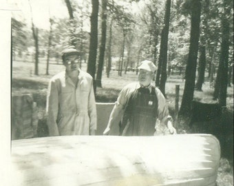 Wooden Canoe on Trailer Old Farmer Standing In Coveralls 1960s Black and White Photo Photograph