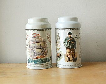 Vintage Pair of British Round Ceylon and Darjeeling Tea Tin Canisters With Orient Ship and Plant Theme