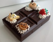 Small plastic case container decorated by delicious looking clay food - Block dark chocolate