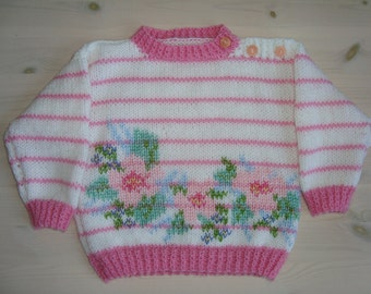 Handknitted babysweater, pink and white with flowers