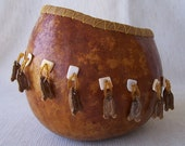 Medium, gold gourd bowl with gourd seed, bead, and shell dangles around. 1233.