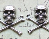 Two Small brass skulls and crossed bones, Sterling silver finish