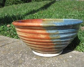 Mid-sized orange and blue bowl with pronounced throw rings