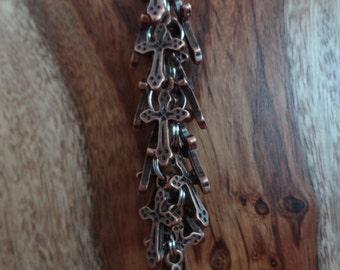 "the ""petite copper cross"" keychain"
