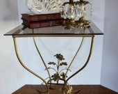 vintage gold Hollywood Regency gilt side table with smoke glass top curved legs decorative gold leaves