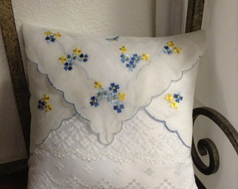 Ring bearer pillow in white lace with blue and yellow flowers.