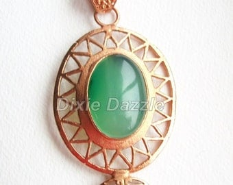 Green onyx gemstone cabochon set in copper filigree pendant with attached bale.