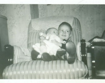 Big Brother Holding Baby Sitting in Chair With Rattle Smile 1940s Vintage Black and White Photo Photograph