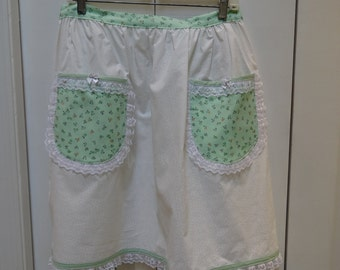 White, half apron with  a mint green floral print, bias tape and  white lace trim.