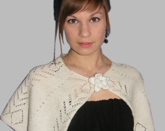 White knitted openwork capelet buttoned up with flower