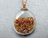 Rainbow seed beads in flat round blown glass copper pendant
