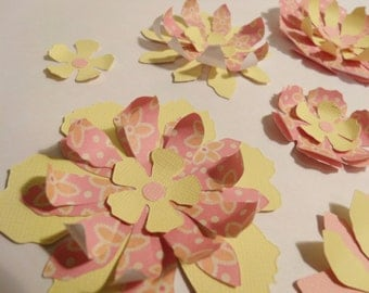 Nine handmade layered flowers with soft pink and yellow tones
