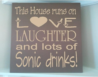 Personalized wooden sign with vinyl quote..This house runs on Love laughter and lots of sonic drinks