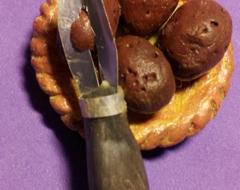 A plate of miniature dollhouse potatoes with peeling tool.