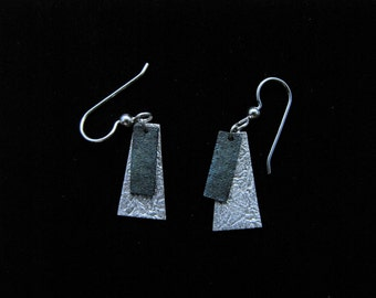 Wedge shaped, silver, dangle earrings with iridescent blue rectangular medallion