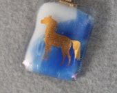 fused glass horse necklace, blue and white background