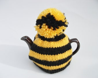 Tea cosy black and gold stripes with a pompom for a small pot. Cornish colours.