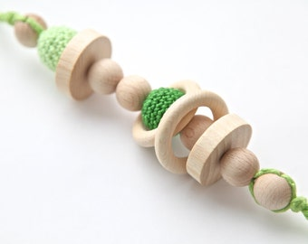 Green big teething rattle for baby. Natural wooden toy with organic cotton.